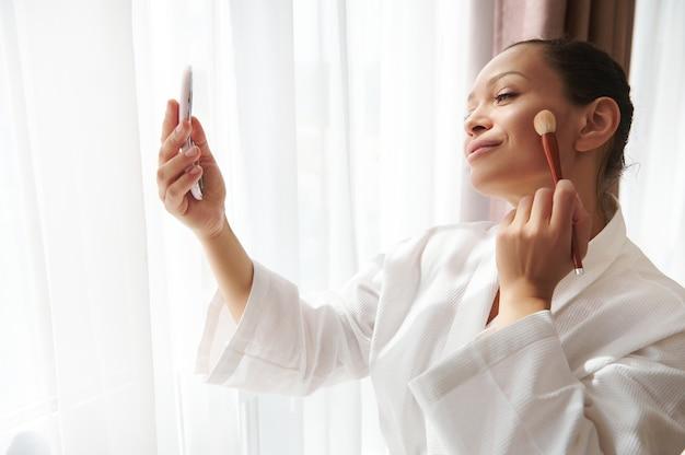 Portrait de beauté d'une jolie femme métisse debout devant la lumière du soleil près de la fenêtre et regardant son reflet dans le miroir tout en appliquant un fard à joues ou un surligneur sur son visage