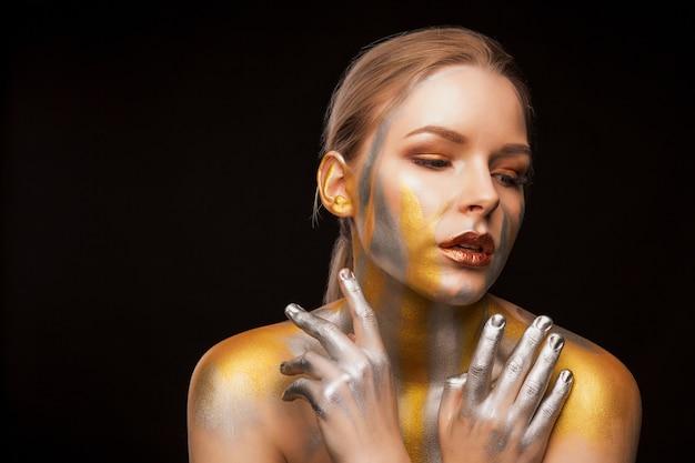 Portrait de beauté d'une jolie femme avec de la peinture dorée et argentée sur ses épaules