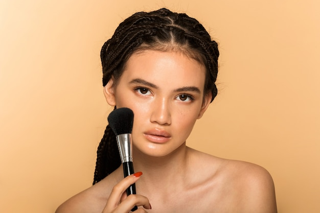 Portrait de beauté d'une jolie jeune femme aux seins nus debout isolée sur un mur beige, appliquant un fard à joues avec un pinceau de maquillage
