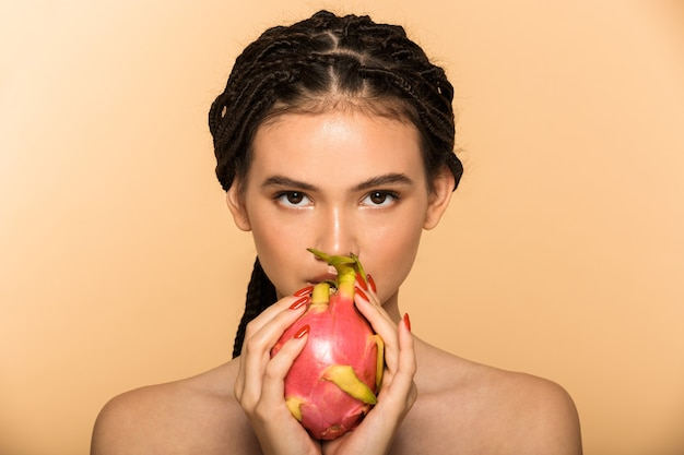 Portrait de beauté d'une jolie jeune femme aux seins nus debout isolée sur un mur beige, posant avec des fruits du dragon