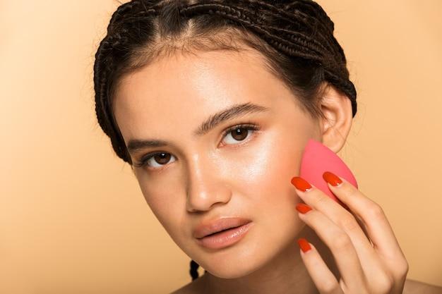 Portrait de beauté d'une jolie jeune femme aux seins nus debout isolée sur un mur beige, tenant une éponge de maquillage sur son visage