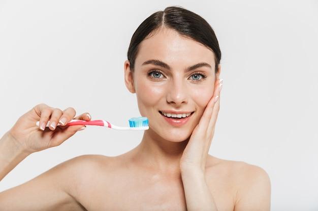 Portrait de beauté d'une jolie jeune femme aux seins nus isolée sur un mur blanc, montrant une brosse à dents avec du dentifrice
