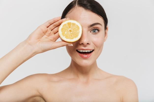 Portrait de beauté d'une jolie jeune femme aux seins nus isolée sur un mur blanc, montrant du citron tranché