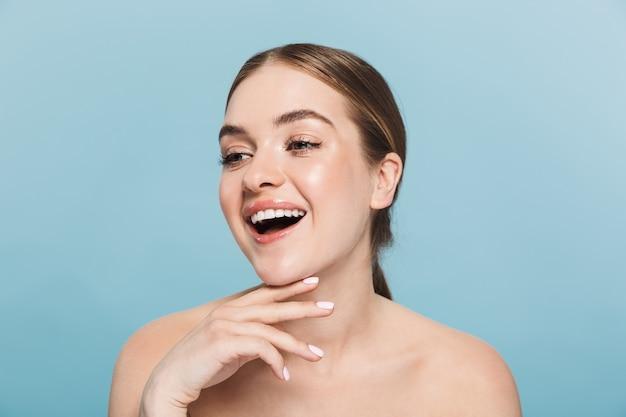 Portrait de beauté d'une jolie jeune femme aux seins nus isolée sur un mur bleu, regardant loin