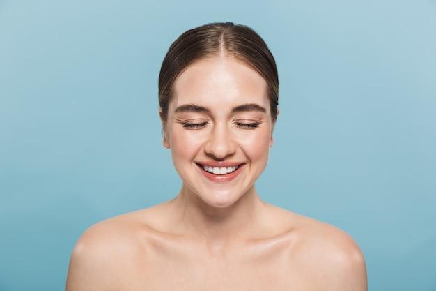 Portrait de beauté d'une jolie jeune femme aux seins nus isolée sur un mur bleu, les yeux fermés