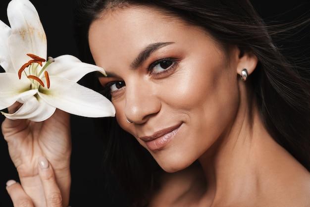 Portrait de beauté d'une jolie jeune femme aux seins nus avec de longs cheveux brune isolée sur un mur noir, posant avec une fleur d'orchidée