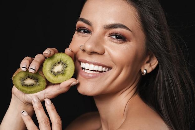 Portrait de beauté d'une jolie jeune femme aux seins nus avec de longs cheveux brune isolée sur un mur noir, posant avec des tranches de kiwi