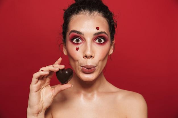 Portrait de beauté d'une jolie jeune femme aux seins nus portant du maquillage debout isolé