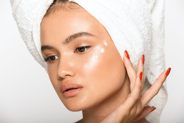 Portrait de beauté d'une jolie jeune femme aux seins nus portant une serviette de bain sur la tête, debout isolée sur un mur blanc, appliquant une crème pour le visage