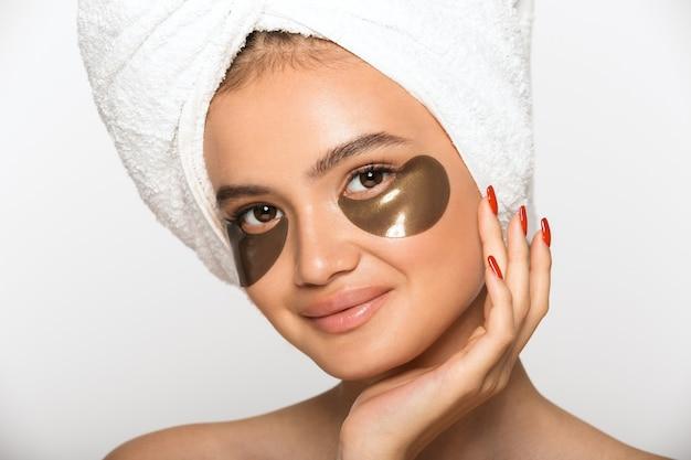 Portrait de beauté d'une jolie jeune femme aux seins nus portant une serviette de bain sur la tête, debout isolée sur un mur blanc, portant des cache-œil cosmétiques