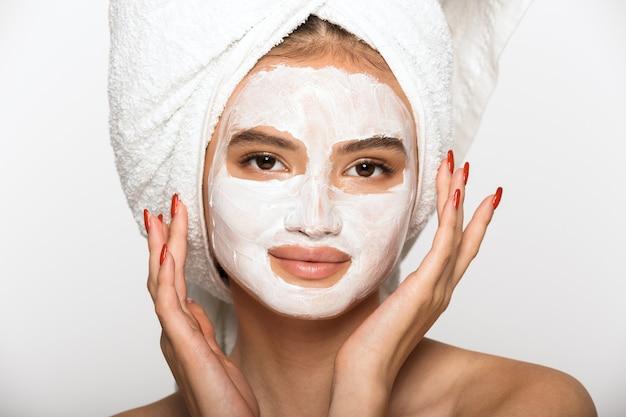 Portrait de beauté d'une jolie jeune femme aux seins nus portant une serviette de bain sur la tête, debout isolée sur un mur blanc, portant un masque facial cosmétique