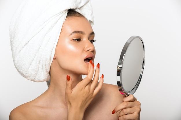 Portrait de beauté d'une jolie jeune femme aux seins nus portant une serviette de bain sur la tête, debout isolée sur un mur blanc, regardant un miroir dans sa main