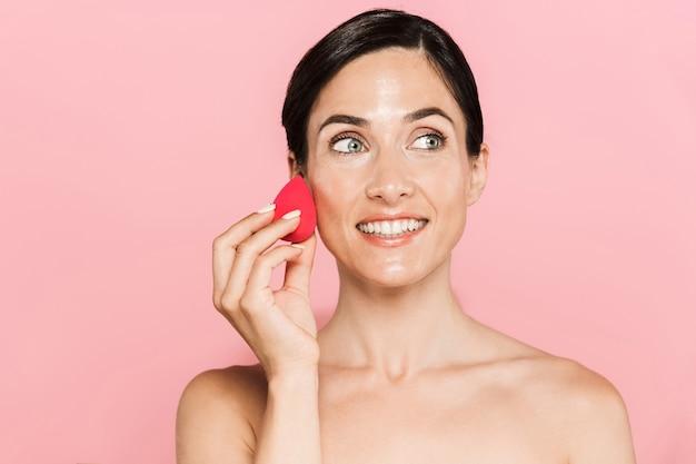 Portrait de beauté d'une jolie jeune femme aux seins nus souriante debout isolée sur un mur rose, à l'aide d'une éponge de maquillage