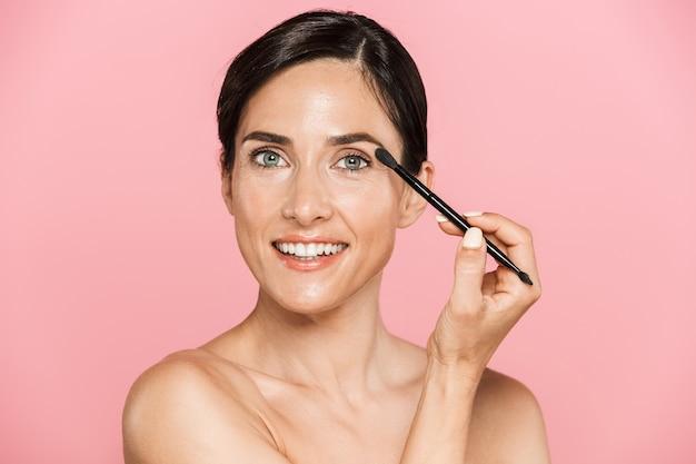 Portrait de beauté d'une jolie jeune femme aux seins nus souriante debout isolée sur un mur rose, appliquant du maquillage avec un pinceau