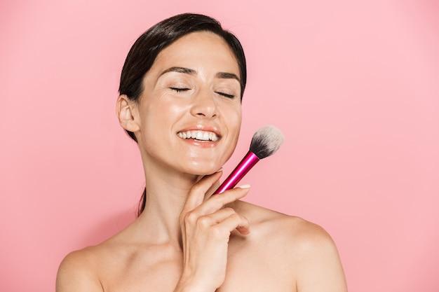 Portrait de beauté d'une jolie jeune femme aux seins nus souriante debout isolée sur un mur rose, tenant un pinceau de maquillage, les yeux fermés