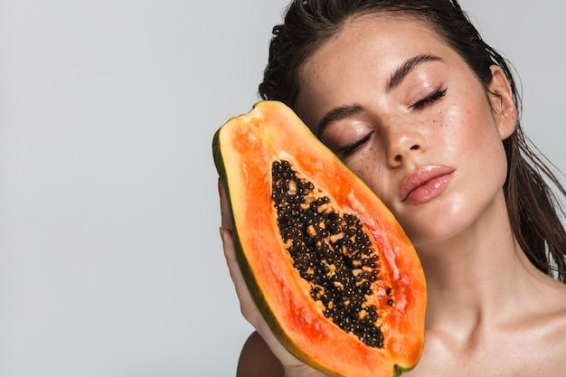 Portrait de beauté d'une jolie jeune femme brune aux seins nus debout isolé sur blanc, posant avec papaye, les yeux fermés