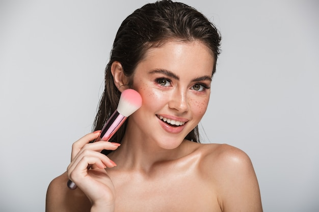 Portrait de beauté d'une jolie jeune femme brune aux seins nus souriante debout isolée sur blanc, tenant un pinceau de maquillage