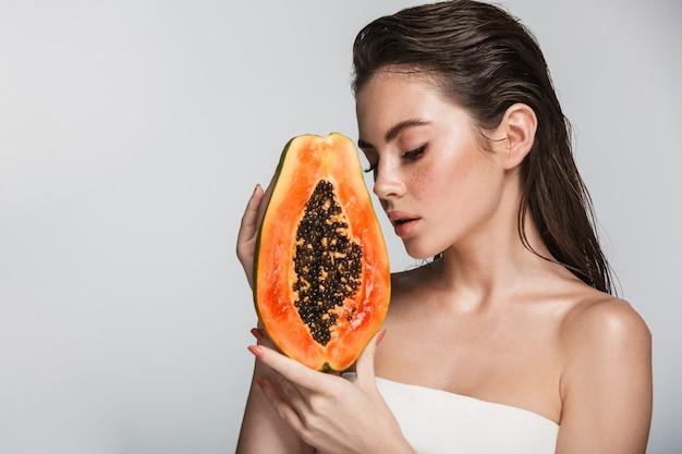 Portrait de beauté d'une jolie jeune femme brune debout isolé sur blanc, posant avec papaye