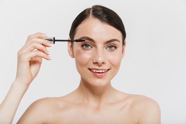 Portrait de beauté d'une jolie jeune femme brune debout isolée sur un mur blanc, appliquant du mascara