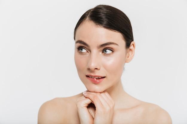 Portrait de beauté d'une jolie jeune femme brune debout isolée sur un mur blanc, en détournant les yeux