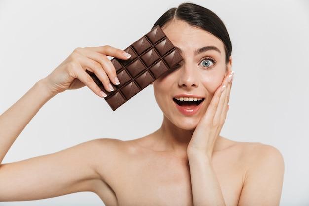 Portrait de beauté d'une jolie jeune femme brune debout isolée sur un mur blanc, montrant une barre de chocolat noir