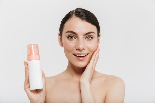 Portrait de beauté d'une jolie jeune femme brune debout isolée sur un mur blanc, montrant une bouteille d'huile pour le visage