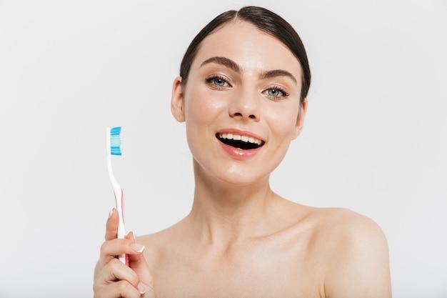 Portrait de beauté d'une jolie jeune femme brune debout isolée sur un mur blanc, montrant une brosse à dents