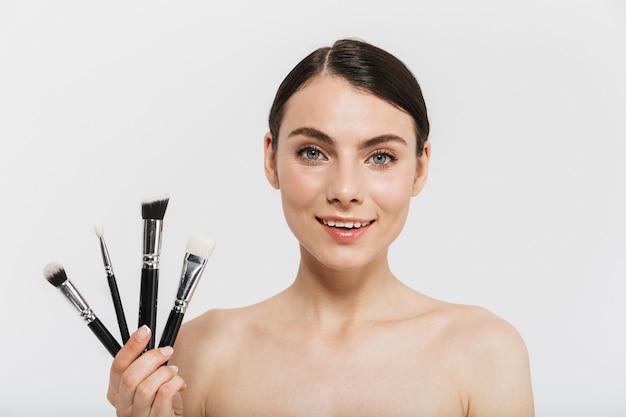 Portrait de beauté d'une jolie jeune femme brune debout isolée sur un mur blanc, montrant des pinceaux de maquillage