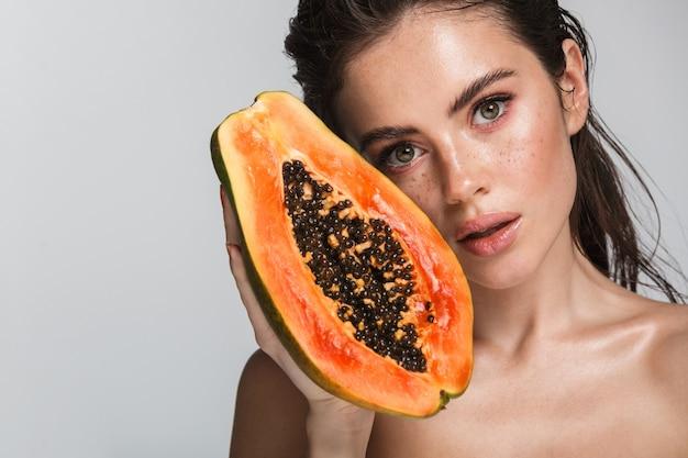 Portrait de beauté d'une jolie jeune femme brune seins nus debout isolé sur blanc, posant avec papaye