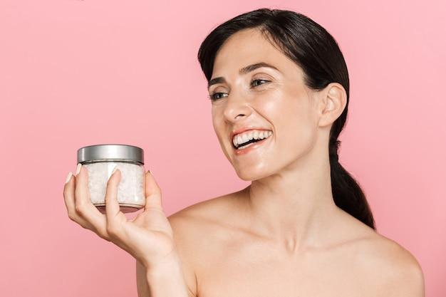 Portrait de beauté d'une jolie jeune femme topless heureuse debout isolée sur un mur rose, tenant du sel de mer