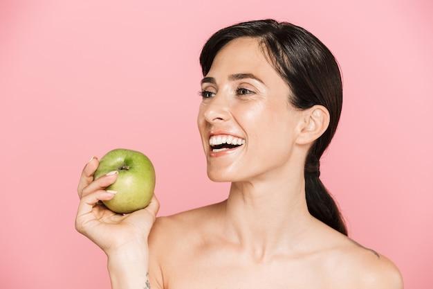 Portrait de beauté d'une jolie jeune femme topless heureuse debout isolée, tenant une pomme verte