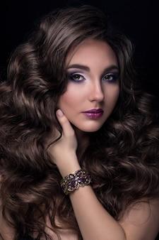 Portrait de beauté de jolie jeune fille portant le bracelet et touchant ses cheveux