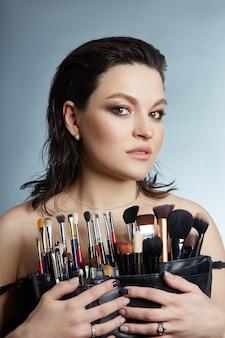 Portrait de beauté d'une maquilleuse. pinceaux de maquillage entre les mains d'une fille