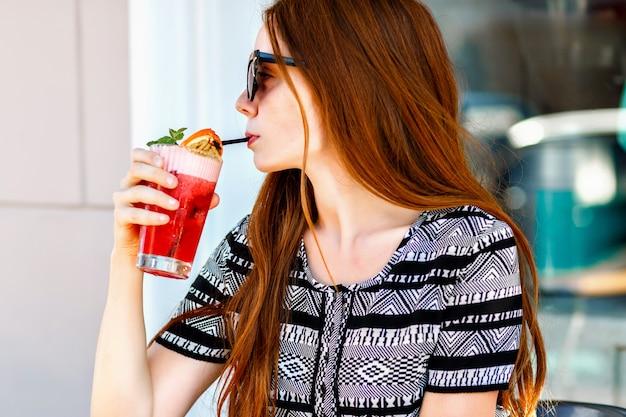 Portrait de beauté de la mode en plein air de femme élégante glamour, cheveux longs incroyables, robe vintage de luxe et lunettes de soleil œil de chat, boire de délicieux cocktails froids, terrasse de café de la ville, voyage, joie, détente.
