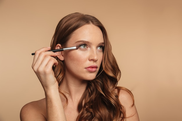 Portrait de beauté de mystérieuse femme au gingembre aux cheveux longs en détournant les yeux tout en appliquant des cosmétiques avec une brosse