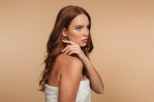 Portrait de beauté de mystérieuse femme au gingembre aux cheveux longs enveloppé dans une serviette posant sur le côté et en détournant les yeux