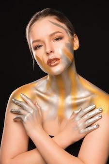 Portrait de beauté d'une superbe dame blonde avec de la peinture dorée et argentée sur ses épaules et son visage
