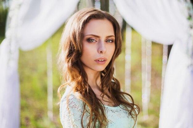 Portrait de beauté d'une très jolie jeune fille. apparence de poupée. femme aux cheveux bruns dans une robe turquoise sur la nature. cheveux longs. lumière naturelle.