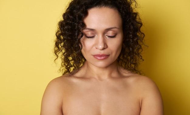 Portrait de beauté d'un visage de femme aux yeux fermés et cheveux bouclés, isolé sur jaune avec espace copie