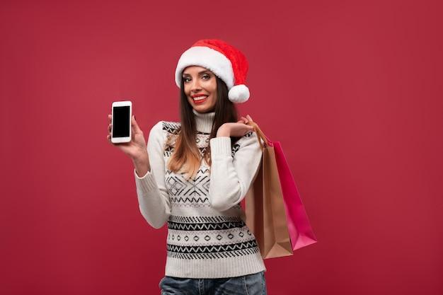Portrait beautifiul caucasian woman santa hat sur mur rouge. concept de noël nouvel an. dents de femme mignonnes souriantes émotions positives avec sac à provisions et téléphone