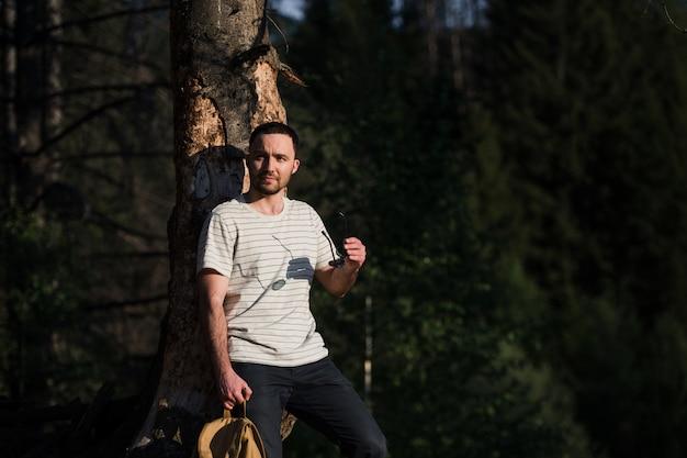 Portrait de beaux-arts d'un homme hipster portant des lunettes de soleil dans une forêt.