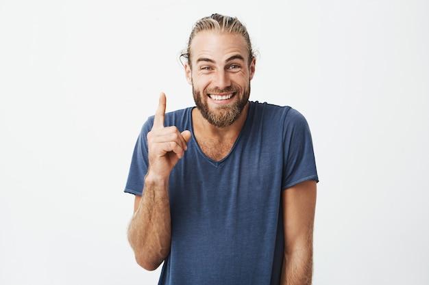 Portrait de beaux hommes joyeux avec coiffure à la mode et barbe, pointant vers le haut