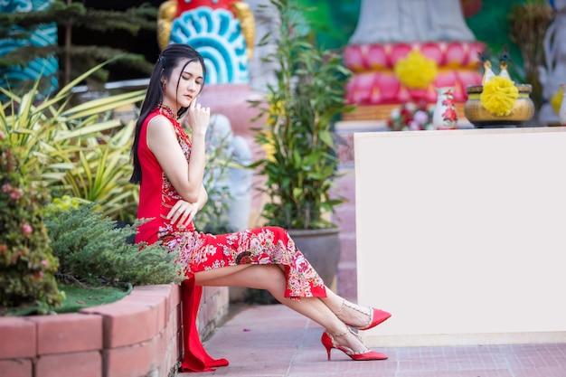 Portrait de beaux sourires asiatique jeune femme portant rouge cheongsam chinois traditionnel, pour le festival du nouvel an chinois au sanctuaire chinois