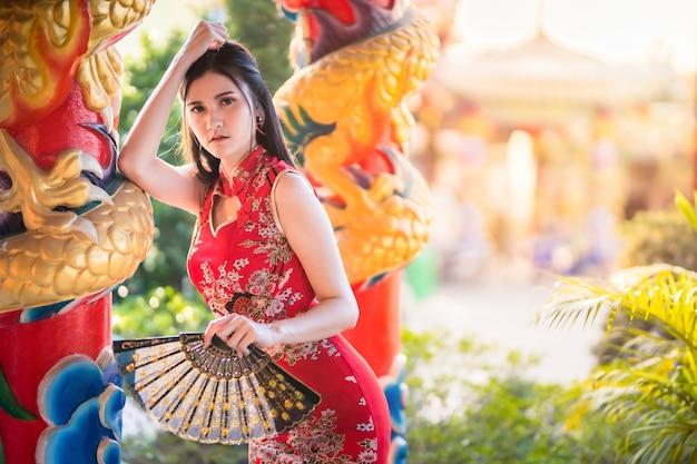 Portrait de beaux sourires asiatique jeune femme portant rouge cheongsam chinois traditionnel, et tenant un ventilateur chinois pour le festival du nouvel an chinois au sanctuaire chinois
