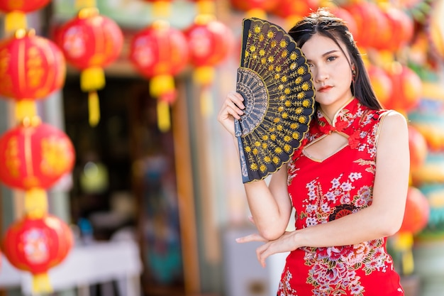 Portrait de beaux sourires asiatique jeune femme portant rouge cheongsam chinois traditionnel
