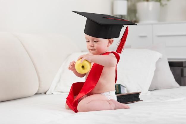 Portrait de bébé de 10 mois en chapeau de graduation et ruban tenant une pomme jaune