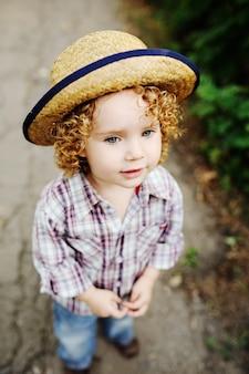Portrait de bébé aux cheveux roux bouclé dans un chapeau.