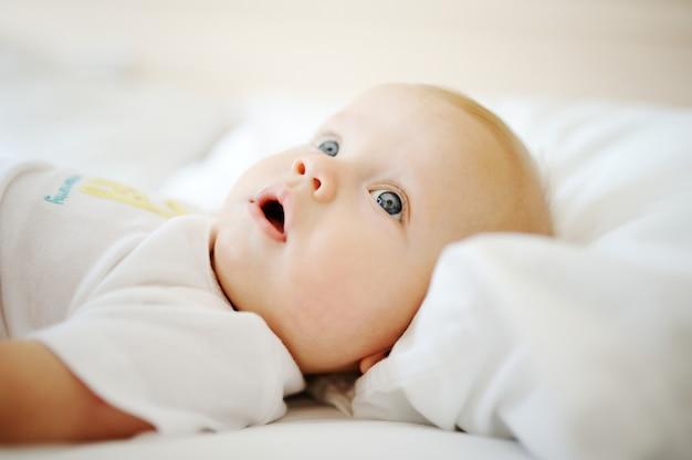 Portrait de bébé aux yeux bleus. un enfant au repos sur un lit