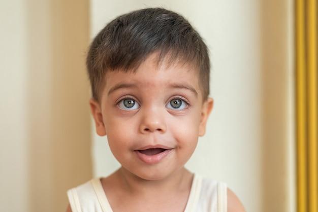 Portrait de bébé aux yeux bleus à la recherche avec une expression calme
