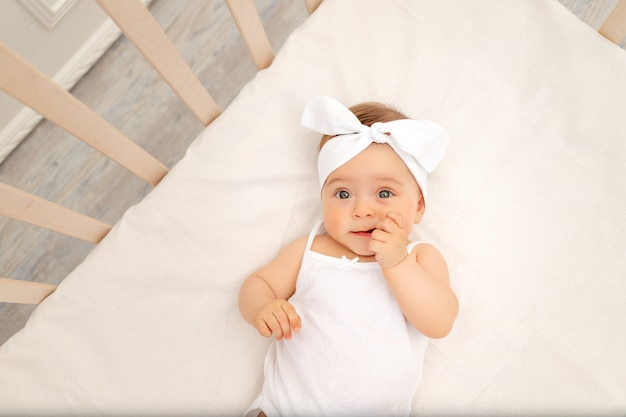 Portrait d'un bébé dans un berceau blanc
